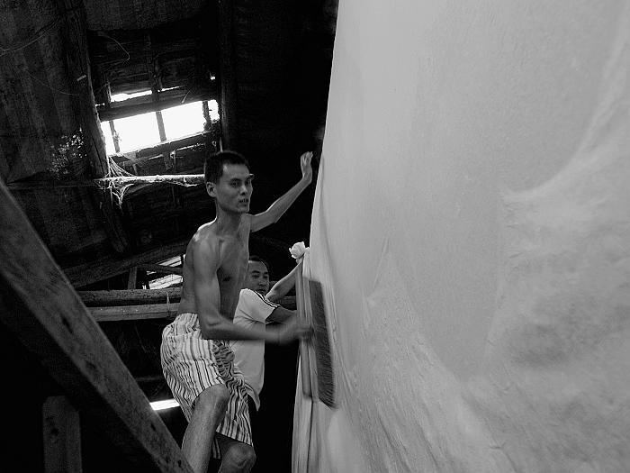 将湿纸(料)贴于 铁板墙之上,刷平整。这就是为何平时所见宣纸的背面有刷子刷过的纹路