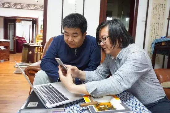 执行主编卢新元与《美术报》首席记者蔡树农讨论稿件