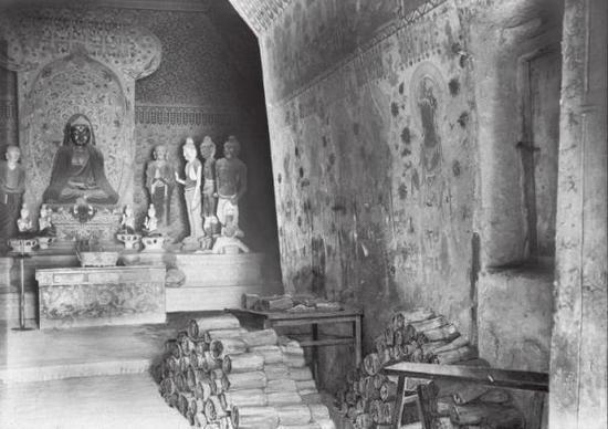 1907年的敦煌藏经洞以及摆在洞窟甬道上的经卷
